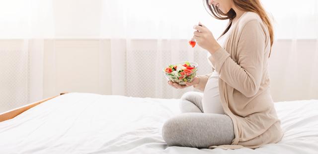 ベッドの上で栄養のあるサラダを食べるママ
