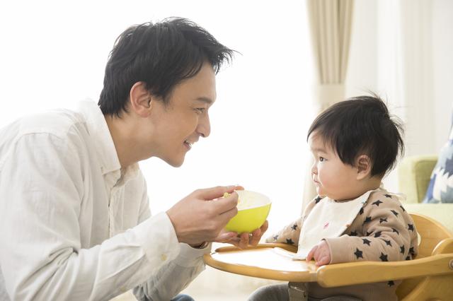 赤ちゃんにご飯をあげるパパ