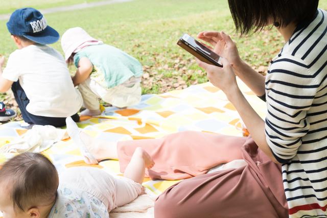近所の公園で子どもの撮影をするママ