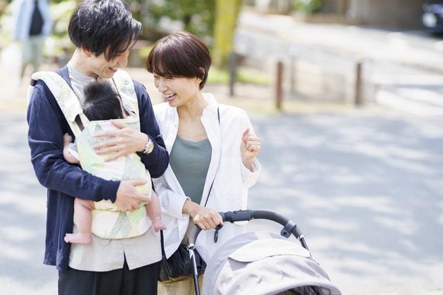 抱っこ紐を使うパパと笑顔のママ