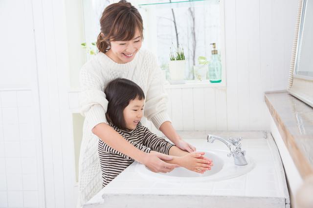 子どもの手洗いに寄り添う母親