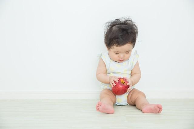 リンゴを触る赤ちゃん